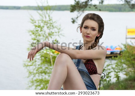 girl with relaxed expression with bikini under denim overall and braid hair-style sitting in the green nature with sea water on background  - stock photo