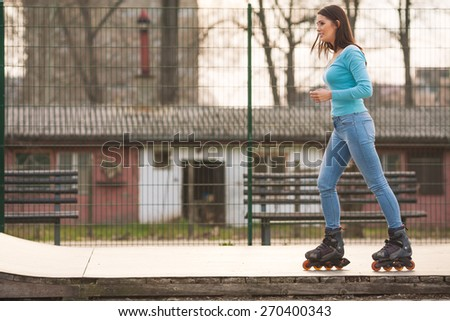 Girl with rollerblades exercising on skate ramp in a park - stock photo