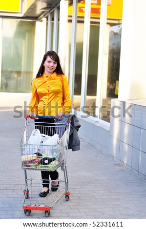 girl with shopping trolley going from shop to car - stock photo