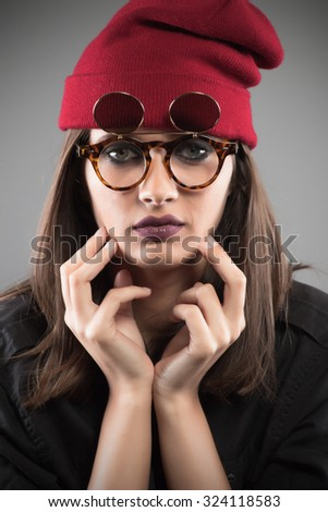Girl with silly eyeglasses and beanie hat - stock photo