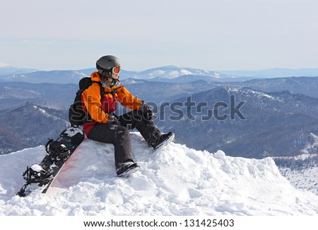 girl with snowboard sitting on top and admire views, Russia, Sheregesh(Kemerovo Region), 2013 - stock photo