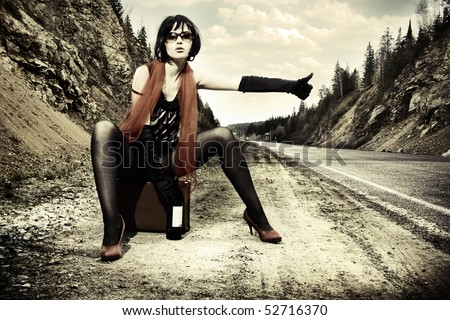 girl with suitcase stops the car - stock photo