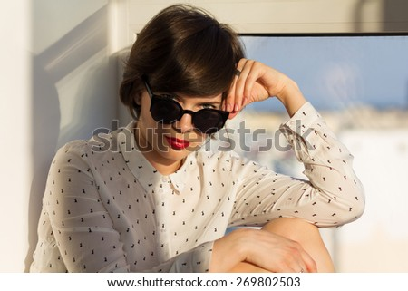 Girl with sunglasses daydreaming sitting by the window - stock photo