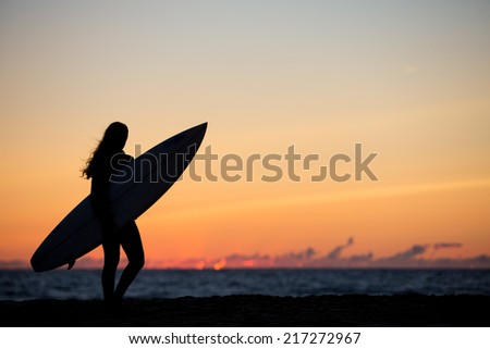 girl with surfboard in sunset  - stock photo