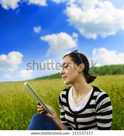 Girl with tablet computer sitting on the grass - stock photo