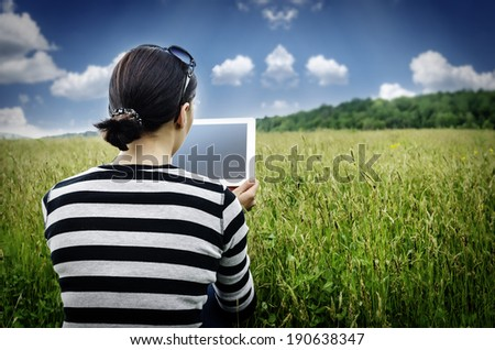 Girl with tablet computer sitting on the grass. Vintage photos. - stock photo