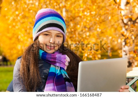 Girl with tablet computer 11 years old sitting in the park on sunny autumn day - stock photo