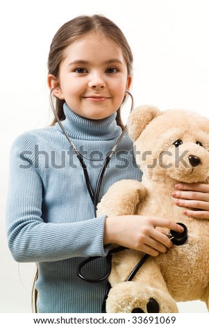 Girl with teddy and stethoscope - stock photo