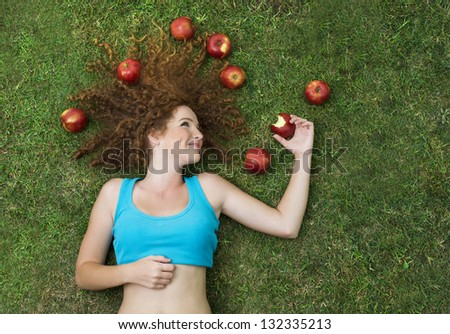 Girl with the apple is lying on the grass and relaxing. - stock photo