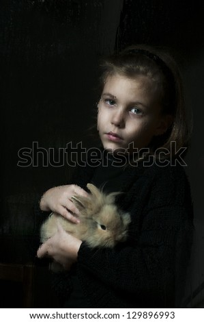 Girl with the bunny behind wet window - stock photo