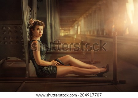 Girl with two pistols sitting on a metal bridge. - stock photo