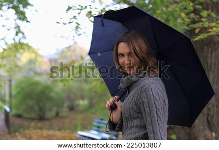 Girl with umbrella in autumn park - stock photo