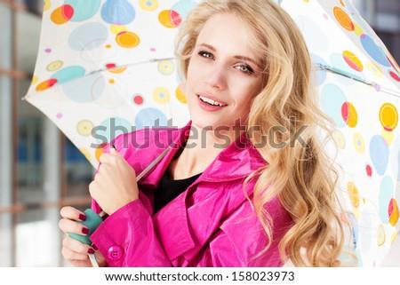 girl with umbrella in pink raincoat - stock photo