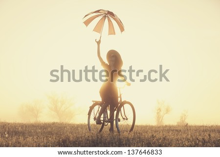 Girl with umbrella on a bike in the countryside in sunrise time - stock photo