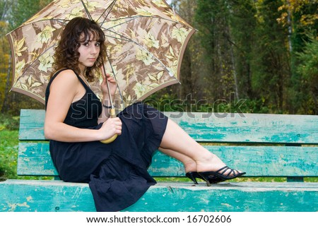 Girl with umbrella sitting on bench at autumn park and smiling. - stock photo