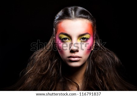girl with unusual make-up on black background - stock photo