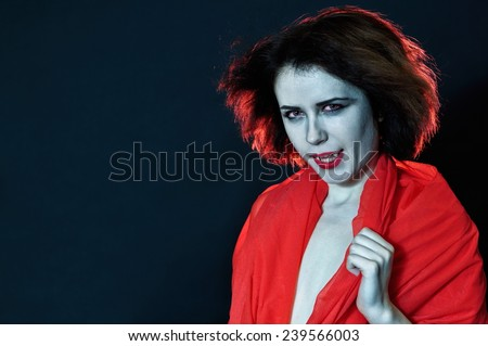 Girl with vampire teeth in red clothes - stock photo