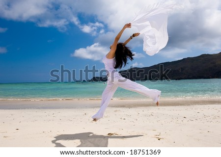girl with white cloth jumping on the beach - stock photo