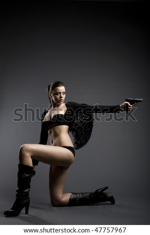 Girl with wings and gun - stock photo