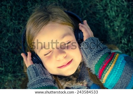Girl with Wireless Headphones Enjoying Music Laying on Grass in a Park. - stock photo