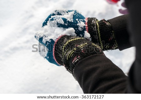 Girl with woolen knitted gloves making snowball, closeup - stock photo
