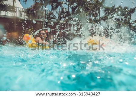 Girl with yellow duck lifebuoy with jumping splash into the summer water pool - stock photo