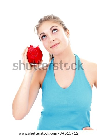 Girl wondering what is inside the piggy bank - stock photo