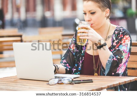 Girl working on her computer outdoor and drinking a pint of beer. She is writing on the keyboard while sitting at open air. There are a smart phone and a pair of glasses on the table. - stock photo
