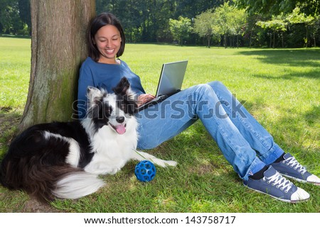 Girl working on her laptop in the park and her dog waiting to play with a ball - stock photo