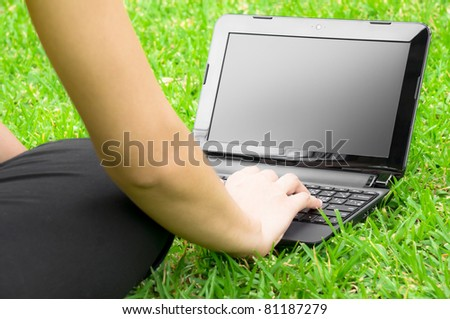 Girl Working with laptop in the field - stock photo