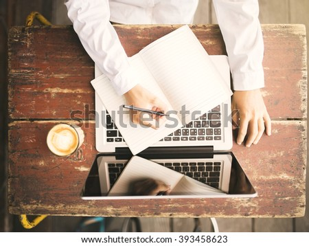 Girl writes in a notebook on a wooden desk with a cup of coffee and laptop - stock photo