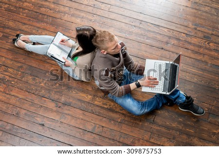 Girl writing in notebook and boy using a laptop leaning on each other on wooden floor.  - stock photo