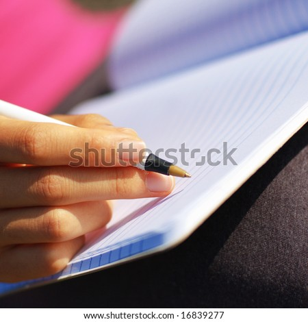 Girl writing in notebook in a field. - stock photo