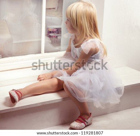 Girl 3 years old in a beautiful white dress near the winter window - stock photo