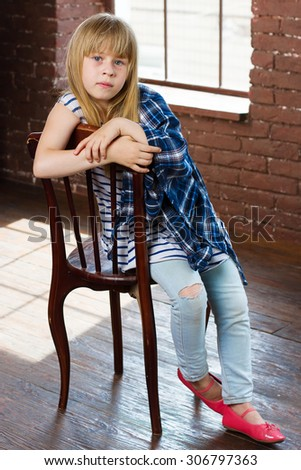 Girl 6 years old in jeans and shirt thrown sits on a chair - stock photo