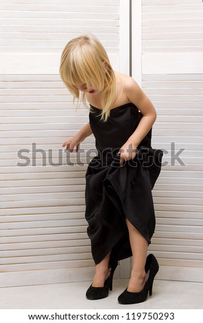 Girl 3 years old in my mother's black dress and high heels - stock photo