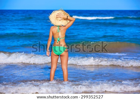 Girl young standing looking at the sea with beach hat rear back view - stock photo