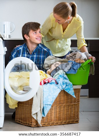 girlfriend and boyfriend doing regular laundry and smiling at home - stock photo