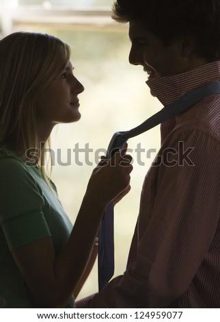 Girlfriend holding boyfriend's necktie - stock photo
