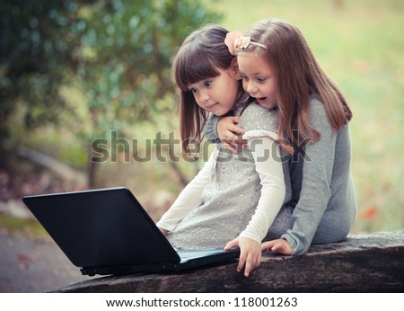 girlfriend in autumn park with laptop - stock photo