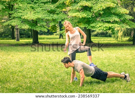 Girlfriend mocking her boyfriend while training in the park - Young man and woman during spring workout and sport activity - Male and female happy couple fitness models exercising after running - stock photo