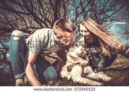 Girlfriend with her boyfriend outdoor in the forest with husky - stock photo