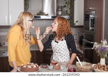 Girlfriends feeding each other with a cake and cooking together in the kitchen at home. - stock photo