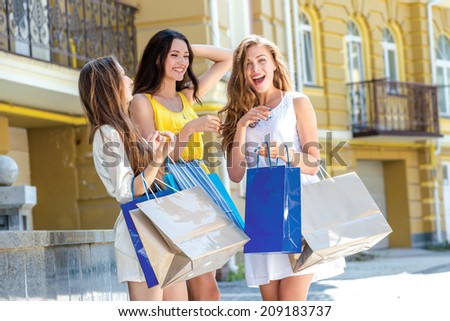 Girlfriends laugh. Girls holding shopping bags and walk around the shops. Smiling girl having fun together - stock photo