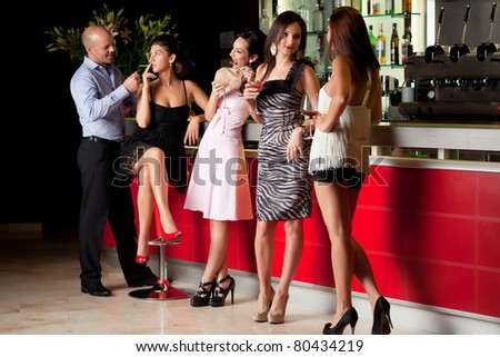 girlfriends talking at the bar, man lighting girl cigarette - stock photo