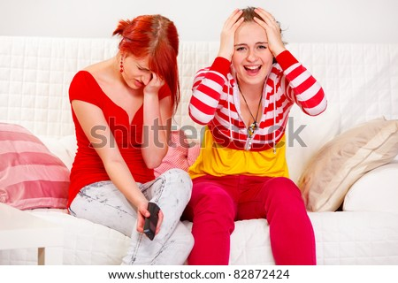 Girlfriends upset by TV program at home - stock photo