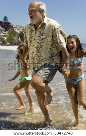Girls and grandfather running through waves - stock photo