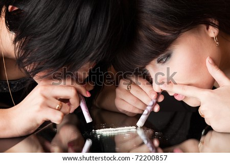 girls are sniffing cocaine (imitation). isolated on a black background - stock photo