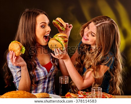 Girls bite burger with two sides. Fastfood humor concept. - stock photo