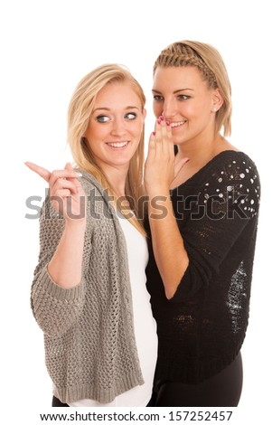 girls chat - woman whispers on friends ear - stock photo